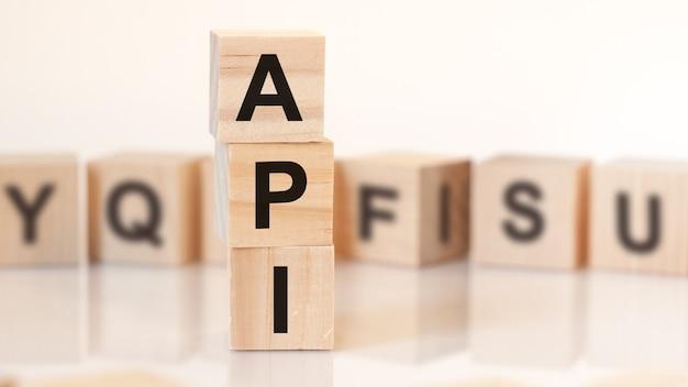 Drewniane kostki z literami api ułożone w koncepcję biznesową piramidy pionowej. api jest skrótem od interfejsu programowania aplikacji