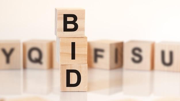 Drewniane kostki z literami bid ułożonymi w koncepcję biznesową piramidy pionowej.