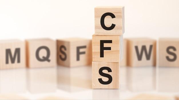 Drewniane kostki z literami cfs ułożone w koncepcję biznesową piramidy pionowej. cfs to skrót od consolidated financial statement (skonsolidowane sprawozdanie finansowe)