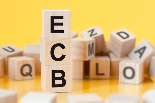 Drewniane kostki z literami ecb ułożonymi w piramidzie pionowej odbicia od powierzchni stołu, koncepcja biznesowa