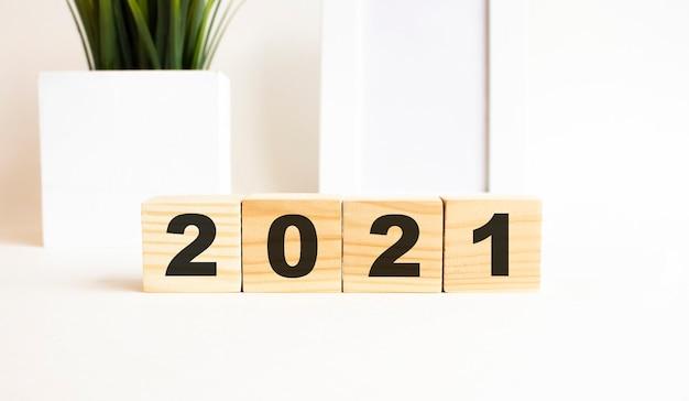 Drewniane kostki z literami na białym stole. słowo to 2021