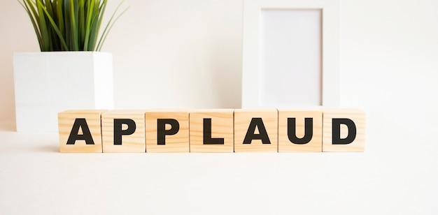 Drewniane kostki z literami na białym stole. słowo to applaud. białe tło z ramką na zdjęcia, roślina domowa.