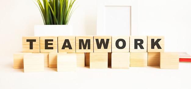 Drewniane kostki z literami na białym stole. słowo to praca zespołowa