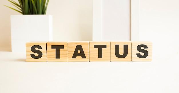 Drewniane kostki z literami na białym stole słowo to status