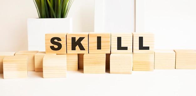 Drewniane kostki z literami na białym stole. słowo to umiejętności. biała powierzchnia z ramką na zdjęcia i rośliną domową