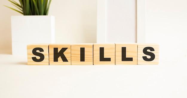 Drewniane kostki z literami na białym stole. to słowo to umiejętności. biała powierzchnia z ramką na zdjęcia i rośliną domową