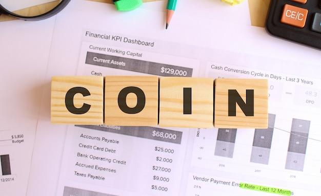 Drewniane kostki z literami na stole. sms o treści coin. koncepcja finansowa.