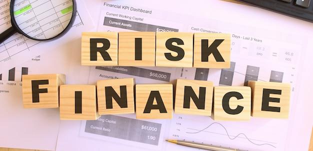 Drewniane kostki z literami na stole. tekst risk finance. koncepcja finansowa.