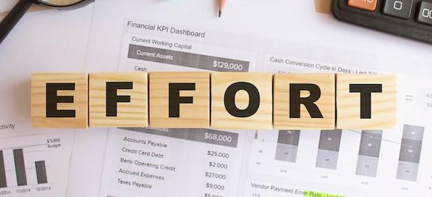 Drewniane kostki z literami na stole w biurze. wyślij sms-a effort. koncepcja finansowa.