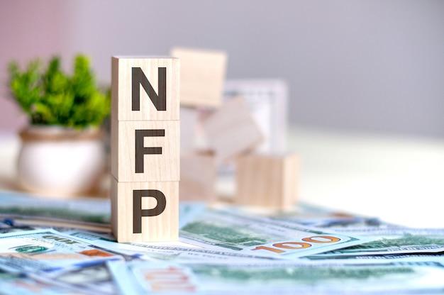 Drewniane kostki z literami nfp ułożone w pionową piramidę na banknotach, zielona roślina doniczkowa. nfp - skrót od niezmiennego tokena, koncepcja biznesowa