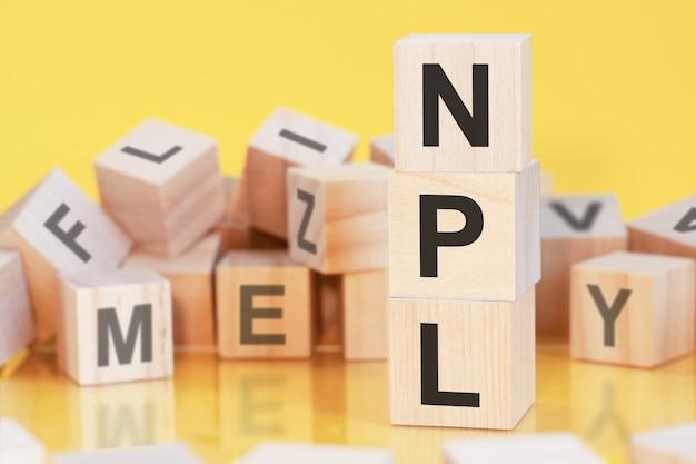 Drewniane kostki z literami npl ułożone w pionową piramidę, żółte tło, odbicie od powierzchni stołu, koncepcja biznesowa. npl - skrót od kredytów zagrożonych