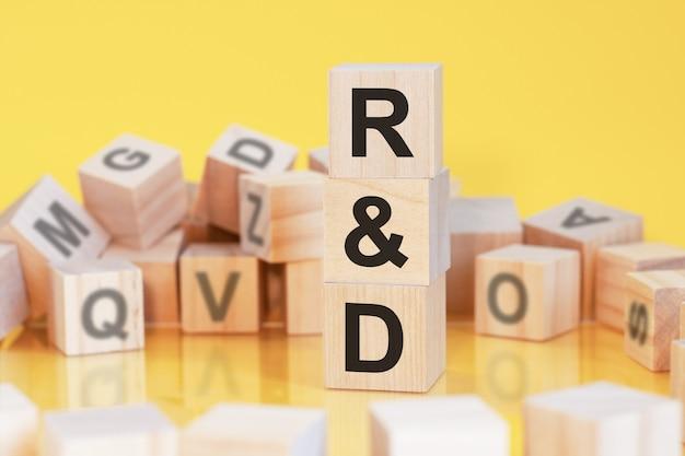 Drewniane kostki z literami r i d ułożone w pionową piramidę, żółte tło, odbicie od powierzchni stołu, koncepcja biznesowa, r i d - skrót od badań i rozwoju