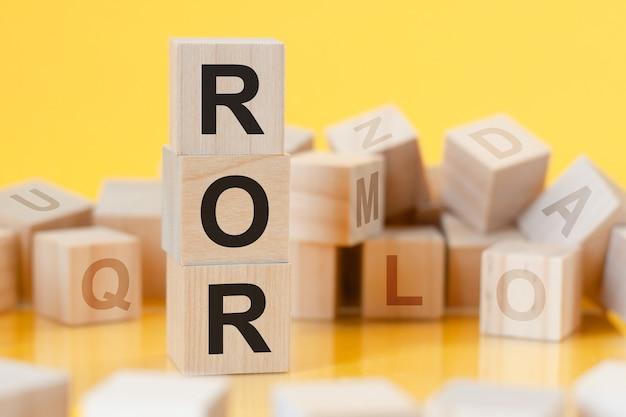 Drewniane kostki z literami ror ułożonymi pionowo piramidą odbicie od powierzchni stołu, koncepcja biznesowa, ror - skrót od stopy zwrotu