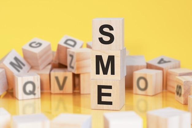 Drewniane kostki z literami sme ułożonymi w pionową piramidę, żółte tło, odbicie od powierzchni stołu, koncepcja biznesowa, sme - skrót dla małych i średnich przedsiębiorstw