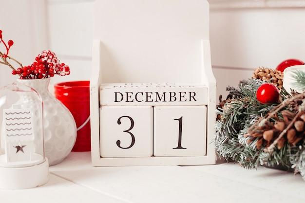 Drewniane kostki z napisem 31 grudnia na tle bożego narodzenia.