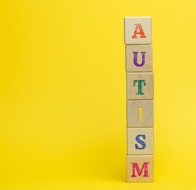 Drewniane kostki z napisem autyzm na żółtej powierzchni