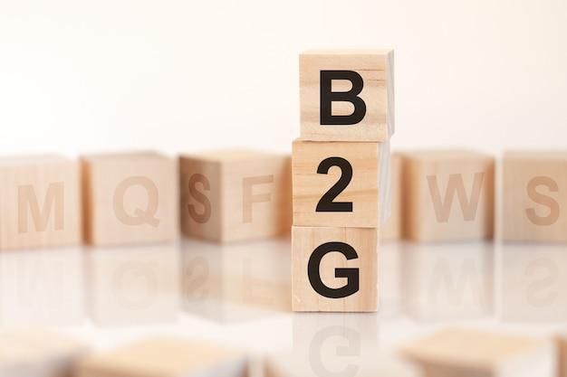 Drewniane kostki z napisem b2g ułożone w pionową piramidę, na jasnej powierzchni rząd drewnianych kostek z literami