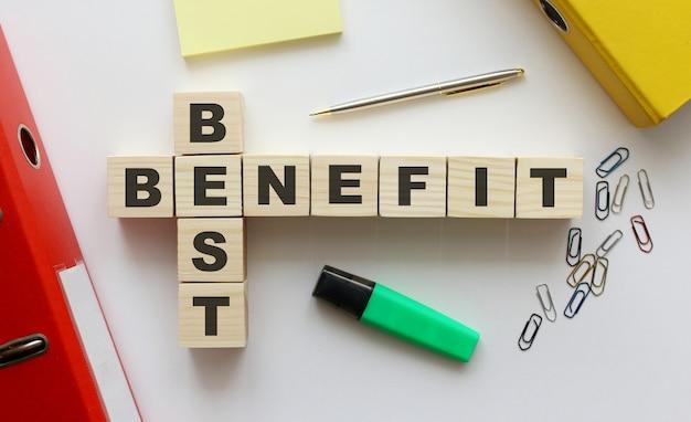 Drewniane kostki z napisem best benefit na biurku. pomysł na biznes.