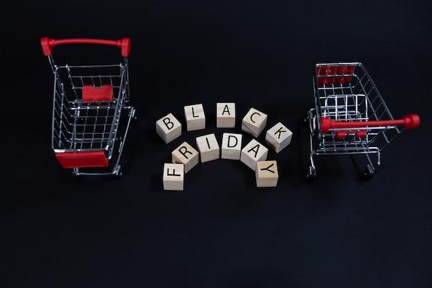 Drewniane kostki z napisem czarny piątek między dwoma wózkami w supermarkecie