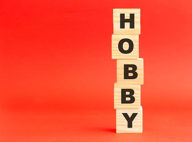 Drewniane kostki z napisem hobby. twój projekt i koncepcja. drewniane kostki na czerwonym tle. wolne miejsce po lewej stronie.