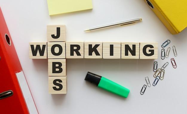 Drewniane kostki z napisem jobs working na biurku. teczka i inne materiały biurowe. miejsce do pracy.