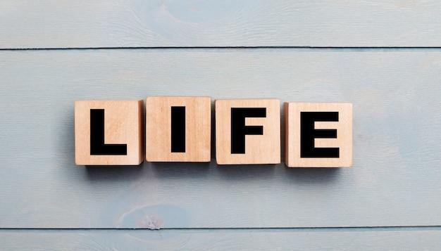 Drewniane kostki z napisem life na jasnoniebieskiej drewnianej ścianie.
