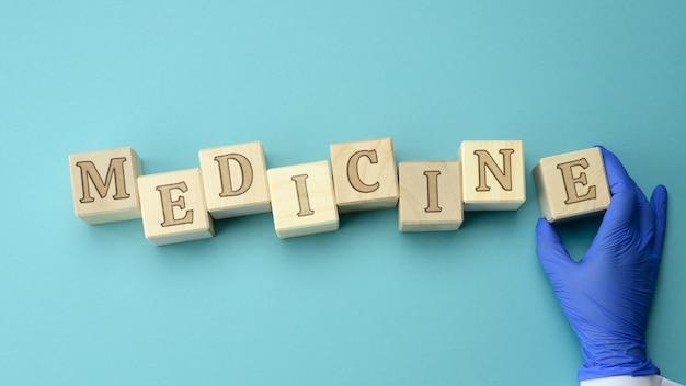 Drewniane kostki z napisem medycyny i ręką lekarza w niebieskiej rękawicy lateksowej, koncepcja ubezpieczenia zdrowotnego