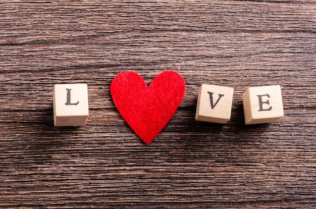 Drewniane kostki z napisem miłość i czerwone serce włókienniczych