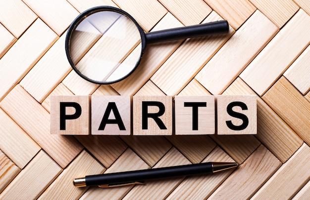Drewniane kostki z napisem parts stoją na drewnianym tle między lupą a długopisem.