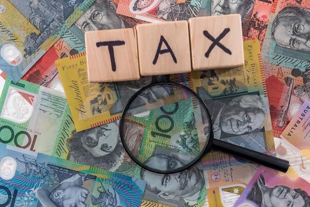 """Drewniane kostki z napisem """"podatek"""" na dolarach australijskich"""