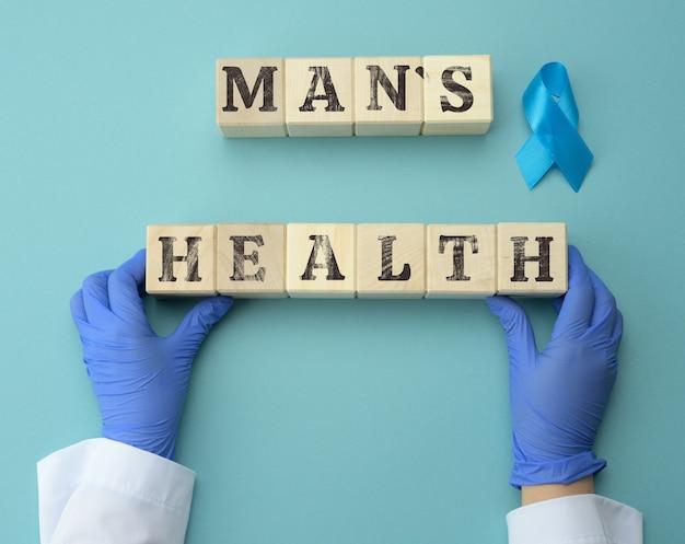 Drewniane kostki z napisem zdrowie mężczyzny i dwie ręce lekarza w niebieskich rękawiczkach