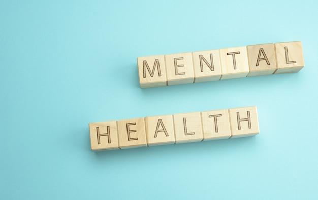 Drewniane kostki z napisem zdrowie psychiczne na niebieskiej powierzchni