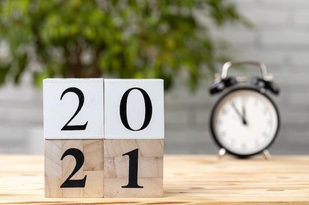 Drewniane kostki z rokiem 2021 i budzikiem na stole roboczym