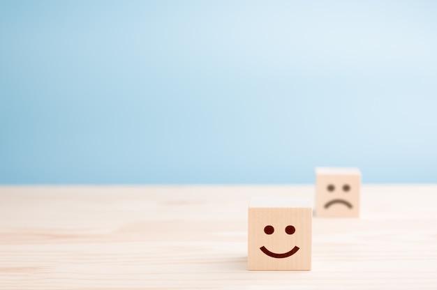 Drewniane kostki z uśmiechniętymi emotikonami i smutną na drewnianym stole
