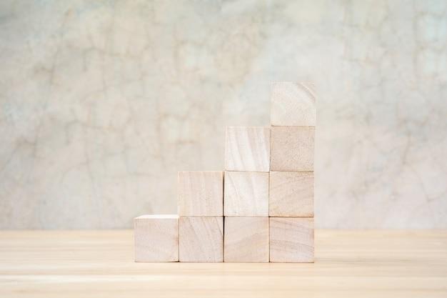Drewniane kostki zabawki na drewnianym stole na szarym tle