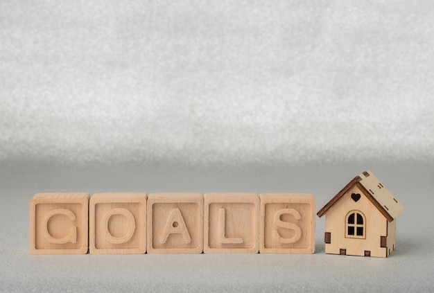 Drewniane kostki ze słowem goal i małym drewnianym domkiem na srebrnym tle koncepcja celu biznesowego
