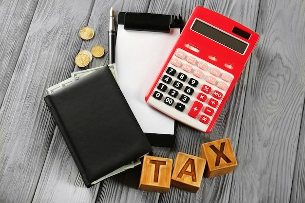 Drewniane kostki ze słowem tax i kalkulatorem na stole