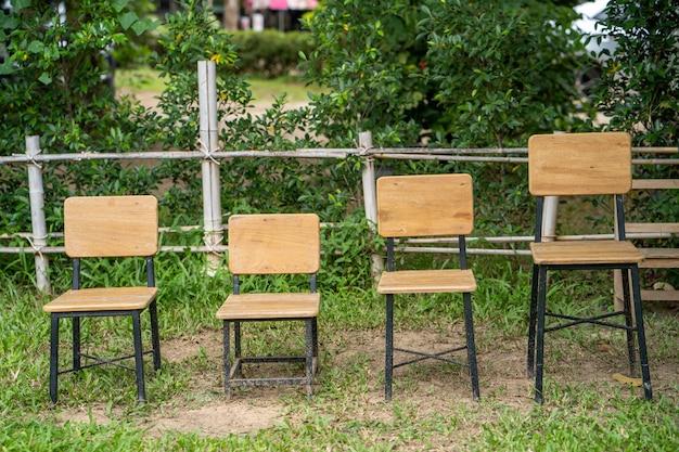 Drewniane krzesła na polu na tle drzewa