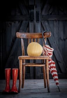 Drewniane krzesło, dynia i parasol z butami