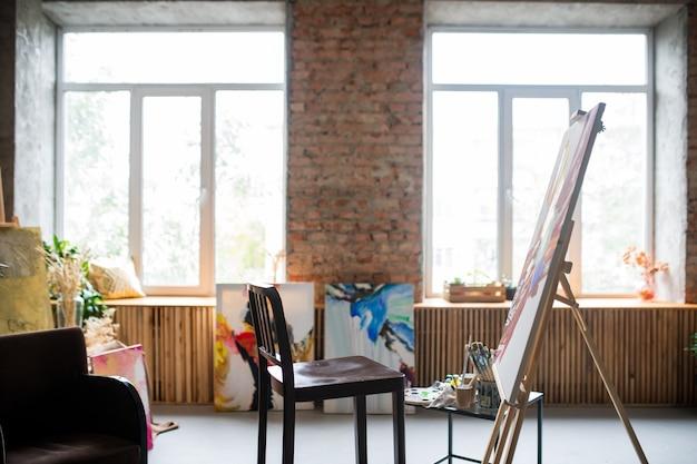 Drewniane krzesło malarza, sztaluga z niedokończonym obrazem, różne urządzenia do prac plastycznych w pracowni lub warsztacie