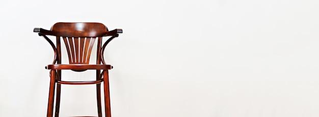 Drewniane krzesło na jasnym tle ściany z miejsca kopiowania tekstu.
