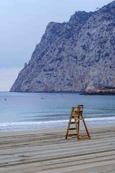 Drewniane krzesło ratownika obok dużego klifu. calpe alicante.