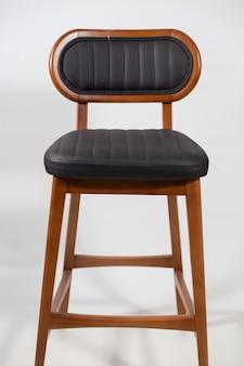 Drewniane krzesło z czarnym skórzanym siedzeniem na białym tle