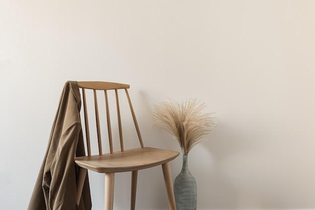Drewniane krzesło z koszulą, trawa pampasowa w wazonie na białej ścianie.