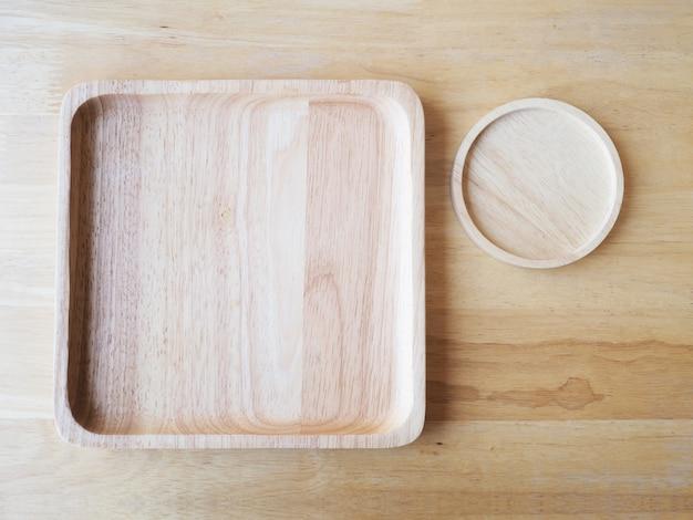 Drewniane kwadratowe i okrągłe talerze na tle drewna