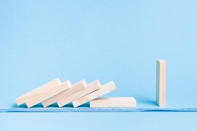 Drewniane kwadratowe kostki domina leżą w rzędzie na niebieskiej powierzchni