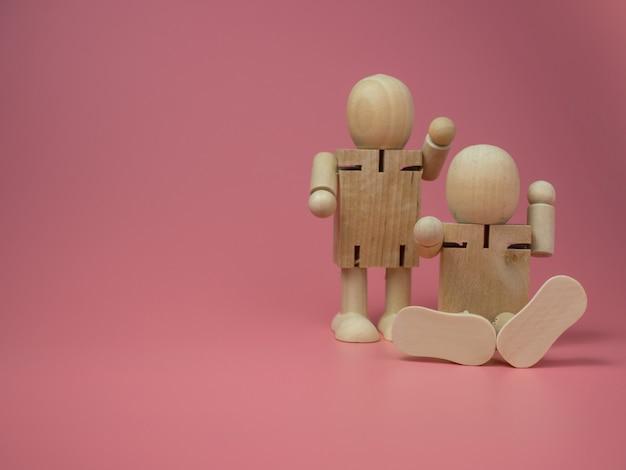 Drewniane lalki siedzące i stojące rozmawiają gesty na różowym tle.