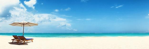 Drewniane leżaki na piaszczystej plaży w pobliżu morza. tło wakacje.