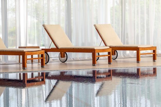 Drewniane leżaki z miękkimi materacami nad wodą na krytym basenie