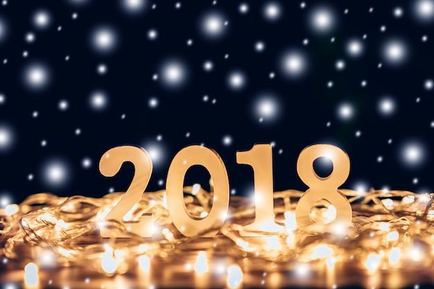 Drewniane liczby tworzy liczbę 2018, dla nowego roku i chrismas zaświecają z śniegiem na drewnie zgłaszają tło.